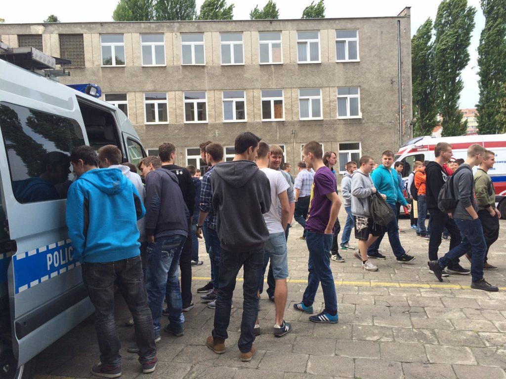 Grupa uczniów przy samochodach podczas wydarzenia